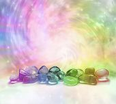 stock photo of reiki  - Selection of rainbow colored crystals on a rainbow colored swirling energy background with sparkles