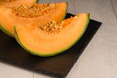 stock photo of honeydew melon  - Juicy honeydew melon on a black slate tray.