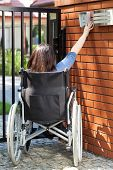 pic of independent woman  - Independent woman on wheelchair dialing intercom vertical