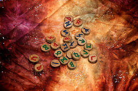 image of rune  - hand carved and painted wooden runes an ancient alphabet known as the futhark are on a colorful hand dyed fabric with small sparkling beads - JPG