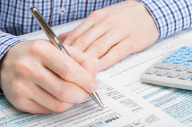 stock photo of cpa  - Male filling out 1040 United States of America Tax Form  - JPG