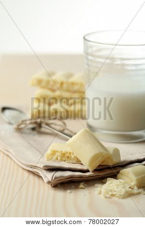 Tasty white porous chocolate and glass of milk, on wooden table. Close up