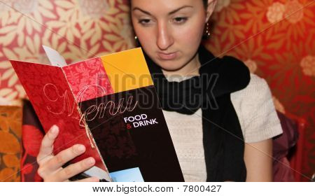 Woman looking in a menu ( menue in focus )