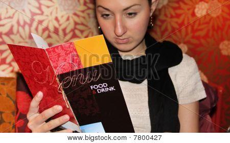 Woman looking in a menu ( menue in focus )