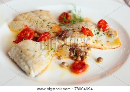 Fried fish fillet with capers and tomatoes in plate