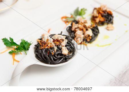 Black pasta with seafood, gourmet dish, close-up