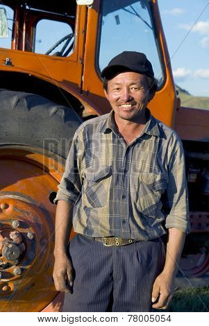 Smiling Mongolian farmer standing next to the tractor.