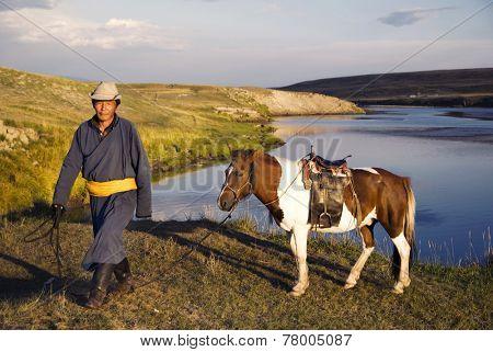 Horse man bringing the horse toward the camera.