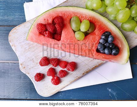 Fresh juicy watermelon slice  with cut out heart shape, filled fresh berries, on cutting board, on color wooden background