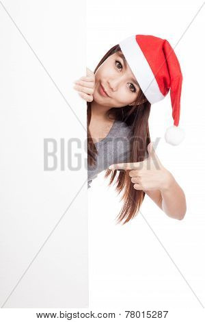 Asian Girl With Santa Hat Peeking From Behind A Blank Sign Point To Blank Sign