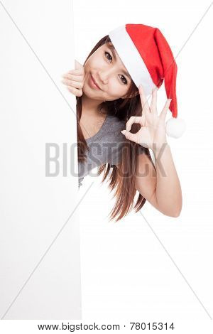 Asian Girl With Santa Hat Peeking From Behind A Blank Sign Show Ok Sign