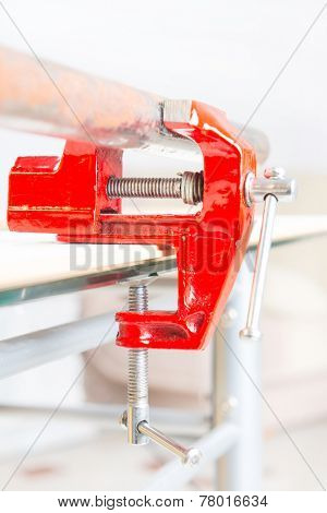 Using a small red vise to hold a rusty pipe