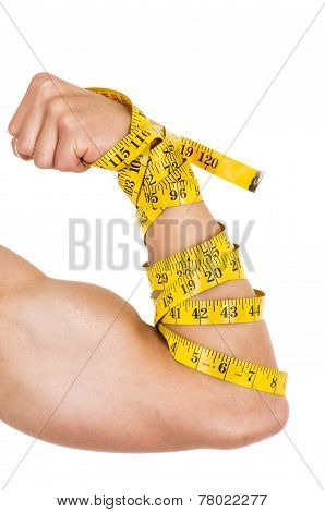 man's arm wrapped in measuring tape showing muscles concept of healthy diet excercise