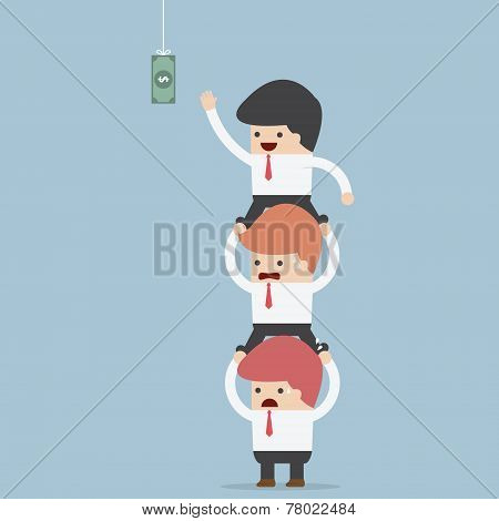 Business People Carrying Each Other To Reach Hanging Money