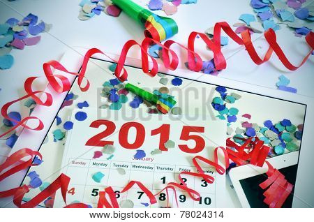 a tablet with a picture of a 2015 calendar on an office desk full of confetti, streamers and a party horn, on an office desk full of confetti, streamers and a party horn