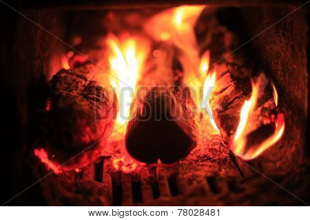 Fire place abstract background - closeup bright blaze flare and firewood - shallow focus depth