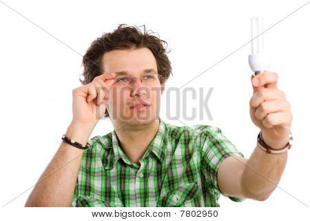 Young Male Inspecting Energy Saving Bulb, Isolated