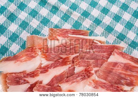 Top view of Serrano ham slices over plate and tablecloth