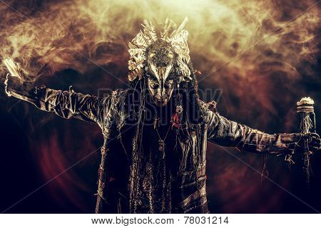 Full length portrait of a male shaman in ethnic dress surrounded by fog. Fantasy concept, magic.