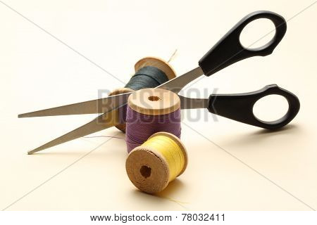 Thread Bobbin And Scissors On The White Background