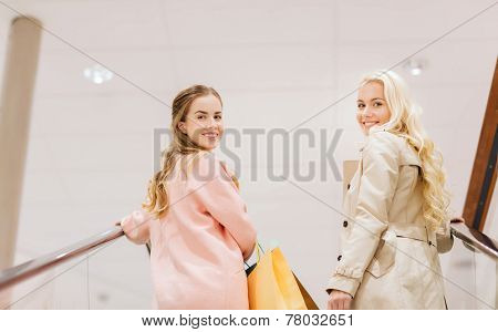 sale, consumerism and people concept - happy young women with shopping bags on escalator in mall