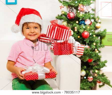 Happy little boy with many xmas presents