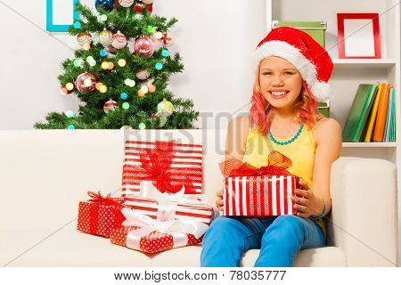Happy teen girl sitting on the sofa with presents