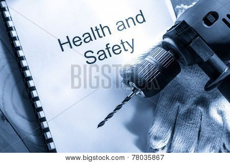 Drill And Gloves On Wooden Background