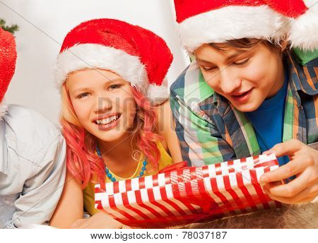 Happy kids in Santa New year hats and with present