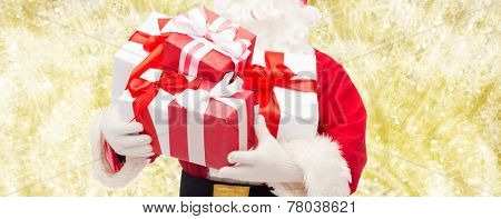 christmas, holidays and people concept - close up of santa claus with gift box over yellow lights background