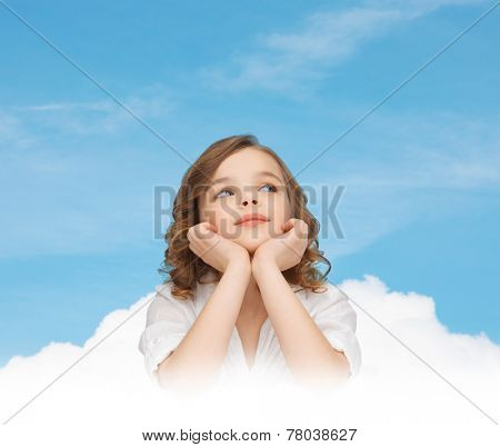 children, childhood, ecology and happy people concept - beautiful girl sitting at table, looking up and dreaming over blue sky and cloud background