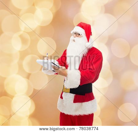 christmas, holidays and people concept - man in costume of santa claus with notepad and pen over beige lights background