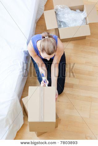 Beautiful Woman Writing On A Box