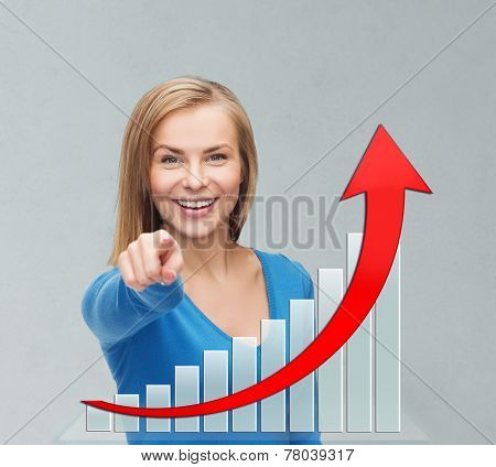business, people, economics, success and gesture concept - smiling young businesswoman pointing at you over gray background and growth chart