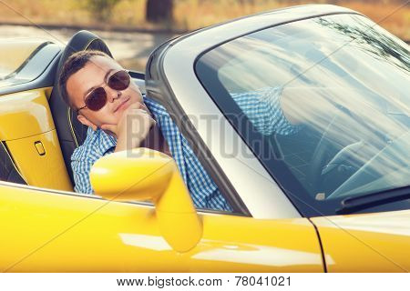 Male Trendy Model Posing In Yellow Convertible Car. Sunglasses. Checkered Shirt