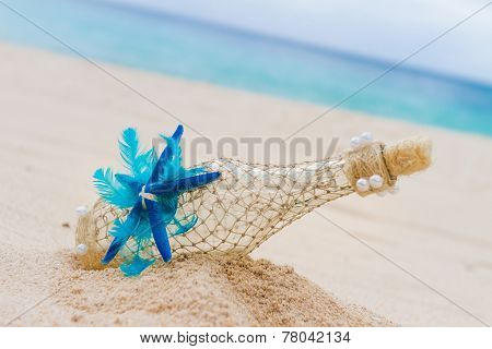 decorated glass bottle on tropical sand beach