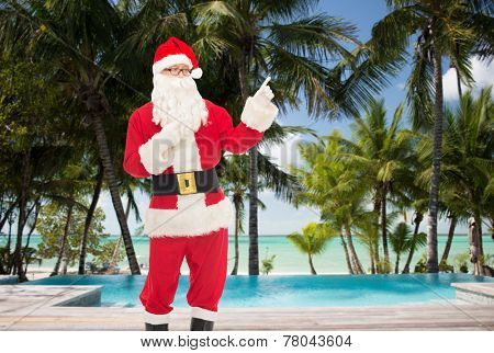 christmas, holidays, gesture, travel and people concept - man in costume of santa claus pointing fingers over swimming pool on tropical beach background
