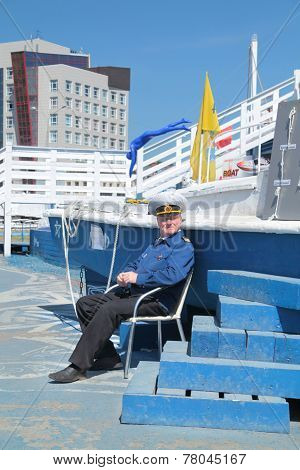 Perm, Russia - Jun 11, 2013: Man In Uniform Captain Sits Beside Boat On Festival White Nights In Per