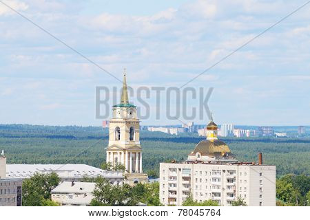 View Of Two Churches And A Residential Building In The City And Forest Separating Neighborhoods