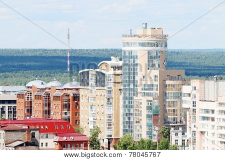 Modern Buildings On Edge Of Large City On Sunny Day With Forest In Background