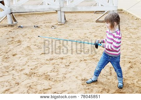 Pretty Little Happy Girl Standing On Sand With Blue Rapier Training For Fencing