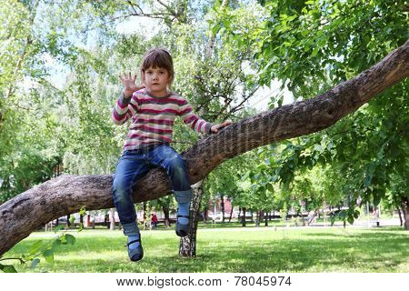 Girl In Striped Sweater And Jeans Waves Hand Sitting On The Tree On Sunny Day