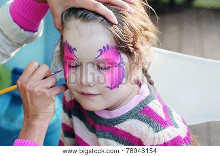 Female Hand Drawing Purple Butterfly On Face Of Beautiful Little Girl