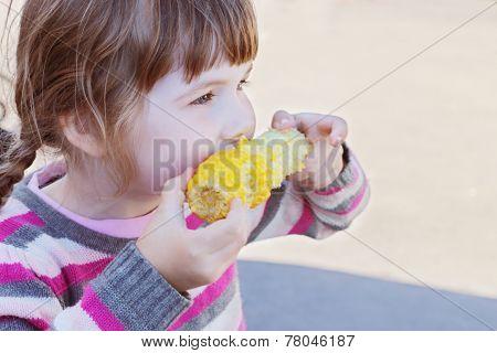 Beautiful Little Girl Eats Boiled Sweet Corn Outdoor At Summer