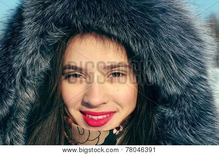 Girl In Fur Coat With Hood Smiles And Looks At Camera In Sunny Winter Day