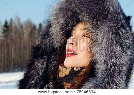 Beautiful Girl In Fur Coat With Hood Looks Away Outdoor In Sunny Winter Day