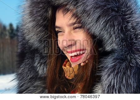 Girl In Fur Coat With Hood Laughs Outdoor In Sunny Winter Day