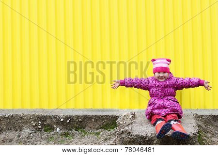 Little Pretty Girl In Gumboots Sits Near Yellow Wall With Arms Outstretched