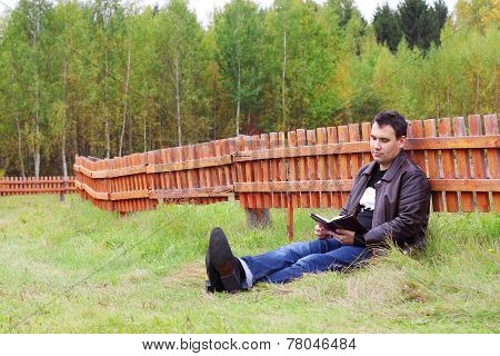 Man Reads Book On Grass Near Orange Wooden Fence At Autumn Day