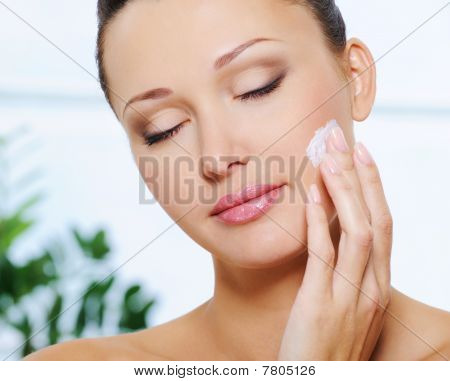 Woman Applying  Moisturizer Cream On Her Cheek